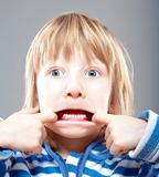 boy with long blond hair making scary faces - isolated on gray