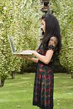 Woman holding a laptop computer outdoors