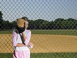 A girl hiding behind a baseball glove