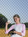 A girl holding a baseball and baseball glove