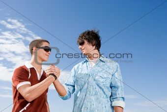 Teenage boys shaking hands