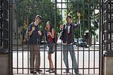 Three high school students behind a gate