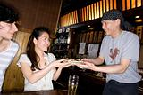 A waiter handing a woman a dish of yakitori