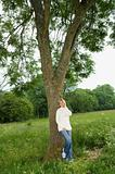 Young woman leaning on a tree