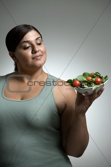 Woman looking at bowl of salad