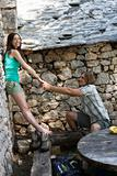 Couple holding hands against stone wall