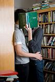 A couple hiding behind a book