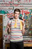 A teenage boy holding half a tie and scissors