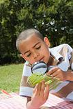 Boy looking at leaf with magnifying glass