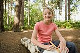 Girl in woods with sketch pad