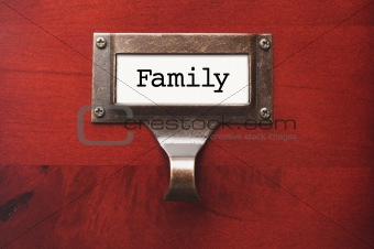 Lustrous Wooden Cabinet with Family File Label in Dramatic LIght.
