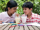 Girl and boy drinking milkshakes