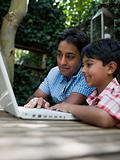Father and son with laptop in garden