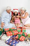 A grandparents and granddaughter in bed with gifts