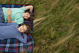 Brother and sister lying in a field