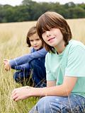 Brother and sister sitting in a field