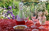 Wine glasses a decanter and a bowl of nuts on a table