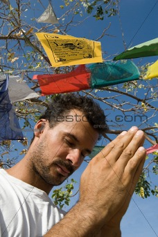 Man praying and prayer flags