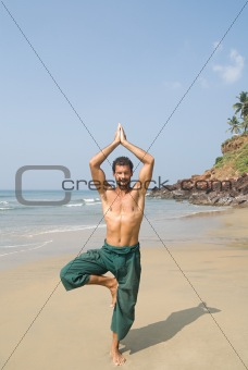 Man doing yoga on beach