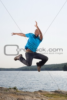 Man jumping by lake