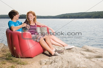 Couple having a beer by lake