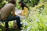 Couple reading newspaper in garden