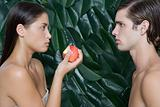 Woman holding half eaten apple opposite man