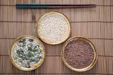 Chopsticks with bowls of rice and pumpkin seeds