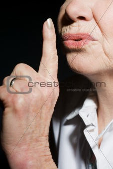 Woman putting finger to lips