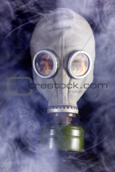 Man is in Gas Mask with Smoke around and Fire reflection