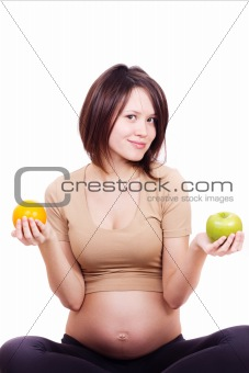 beautiful pregnant woman holding an orange and an apple in her hands