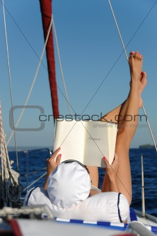 Young woman reading and sunbathing on sail boat