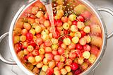 watering fresh cherry in colander