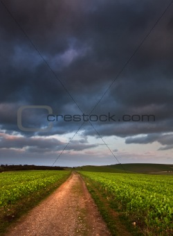 Countryside landscape path leading through fields towards dramat