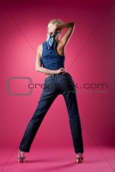 Tall sexy girl posing in jeans on pink background