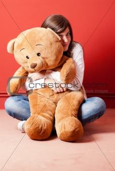 Young woman embracing teddy bear sitting on floor