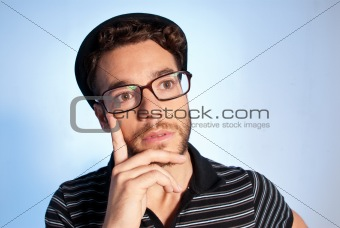 Young man modern nerd thinking wide angle portrait blue background