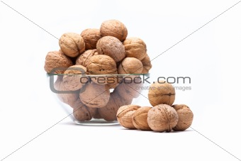 Walnuts are a lie in a glass bowl isolated on a white background