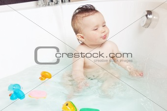 Cute baby playing with water and showing tongue while taking a bath