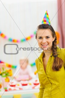 Portrait of smiling mom at baby birthday party