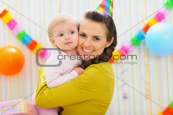 Portrait of happy mother and baby at birthday party