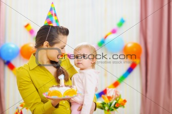 Portrait of baby and mother with birthday party cake
