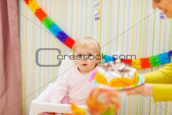 Mom carries cake for surprised baby