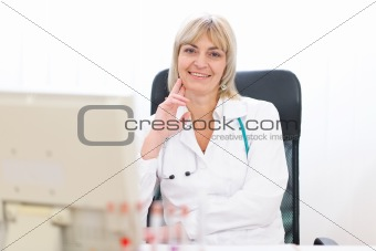 Portrait of happy mature doctor woman at laboratory