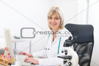 Portrait of smiling mature doctor woman at laboratory