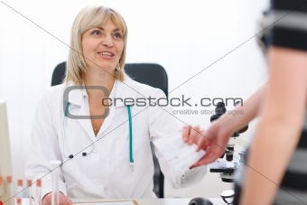 Senior doctor woman giving prescription to patient