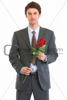 Portrait of happy man in suit with rose in hand