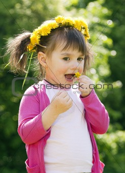 A smiling girl sitting on the dandelion field with the dandelion