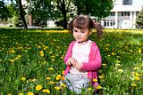 A smiling girl sitting on the dandelion field wearing a pink sh