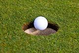 A golf ball is going in an hole